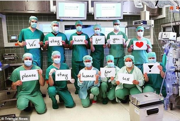 Các y bác sĩ trên toàn thế giới đồng loạt giơ cao thông điệp ý nghĩa: Chúng tôi đang làm việc vì các bạn còn các bạn hãy ở nhà vì chúng tôi - Ảnh 1.