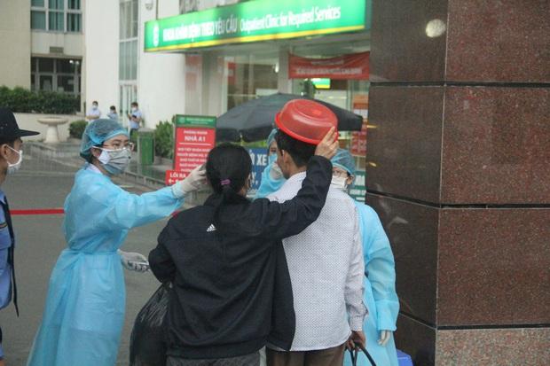 Cán bộ nhân viên BV Bạch Mai đội mưa kiểm tra thân nhiệt từng người vào viện, ngừng khám theo yêu cầu để chống dịch COVID-19 - Ảnh 15.