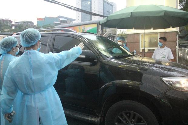 Cán bộ nhân viên BV Bạch Mai đội mưa kiểm tra thân nhiệt từng người vào viện, ngừng khám theo yêu cầu để chống dịch COVID-19 - Ảnh 11.