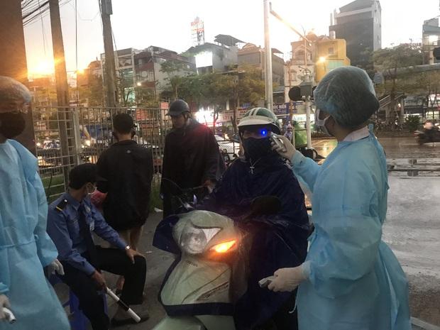 Cán bộ nhân viên BV Bạch Mai đội mưa kiểm tra thân nhiệt từng người vào viện, ngừng khám theo yêu cầu để chống dịch COVID-19 - Ảnh 16.