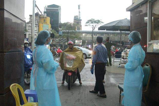 Cán bộ nhân viên BV Bạch Mai đội mưa kiểm tra thân nhiệt từng người vào viện, ngừng khám theo yêu cầu để chống dịch COVID-19 - Ảnh 19.