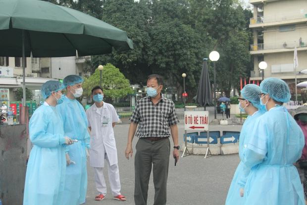 Cán bộ nhân viên BV Bạch Mai đội mưa kiểm tra thân nhiệt từng người vào viện, ngừng khám theo yêu cầu để chống dịch COVID-19 - Ảnh 6.