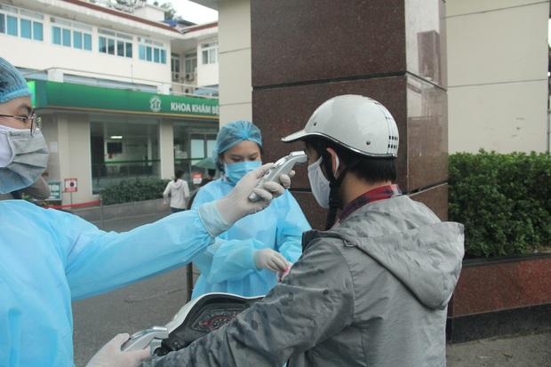 Cán bộ nhân viên BV Bạch Mai đội mưa kiểm tra thân nhiệt từng người vào viện, ngừng khám theo yêu cầu để chống dịch COVID-19 - Ảnh 9.