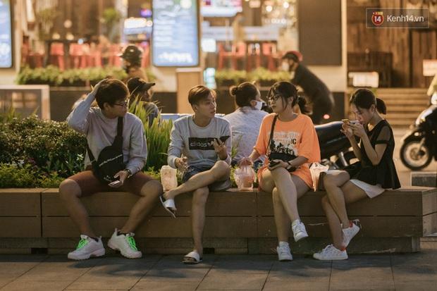 """Sài Gòn nhộn nhịp trong buổi tối nghỉ lễ đầu tiên: Khu vực trung tâm dần trở nên đông đúc, nhiều người lo sợ vẫn """"kè kè"""" chiếc khẩu trang bên mình - Ảnh 9."""