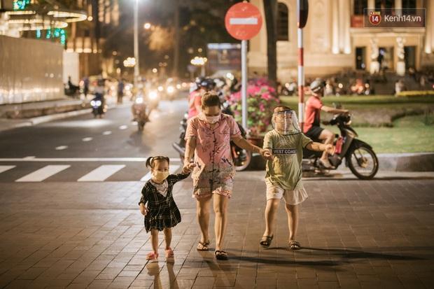 """Sài Gòn nhộn nhịp trong buổi tối nghỉ lễ đầu tiên: Khu vực trung tâm dần trở nên đông đúc, nhiều người lo sợ vẫn """"kè kè"""" chiếc khẩu trang bên mình - Ảnh 32."""
