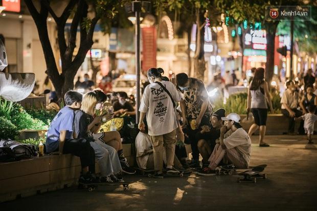 """Sài Gòn nhộn nhịp trong buổi tối nghỉ lễ đầu tiên: Khu vực trung tâm dần trở nên đông đúc, nhiều người lo sợ vẫn """"kè kè"""" chiếc khẩu trang bên mình - Ảnh 8."""