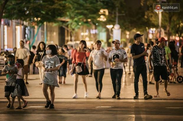 """Sài Gòn nhộn nhịp trong buổi tối nghỉ lễ đầu tiên: Khu vực trung tâm dần trở nên đông đúc, nhiều người lo sợ vẫn """"kè kè"""" chiếc khẩu trang bên mình - Ảnh 5."""