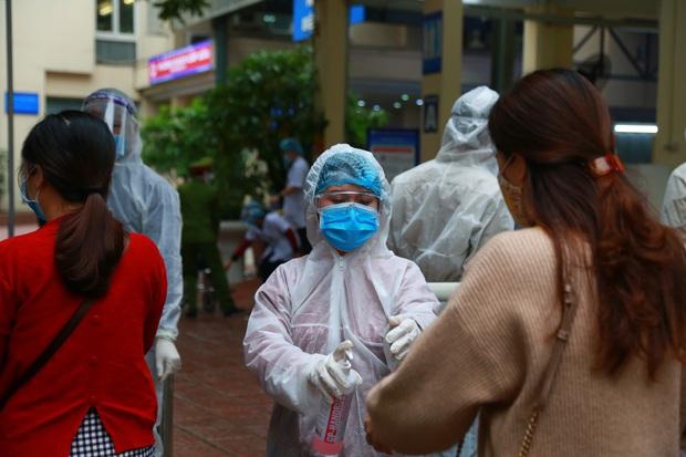 Ảnh: Bệnh viện lập chốt kiểm tra y tế mùa dịch Covid-19, thai phụ đội mũ chống giọt bắn, được chồng đưa đi khám - Ảnh 2.