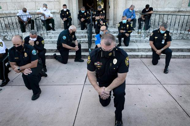 Nhiều cảnh sát Mỹ bất ngờ bỏ dùi cui, quỳ gối đồng hành cùng người biểu tình để tưởng niệm nạn nhân bị cảnh sát chẹt cổ chết - Ảnh 3.