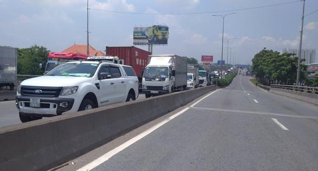 Xe tải rớt bánh lật trên quốc lộ 1A ở Sài Gòn, nhiều người thoát chết, giao thông ùn ứ kéo dài   - Ảnh 6.