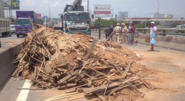 Xe tải rớt bánh lật trên quốc lộ 1A ở Sài Gòn, nhiều người thoát chết, giao thông ùn ứ kéo dài   - Ảnh 1.