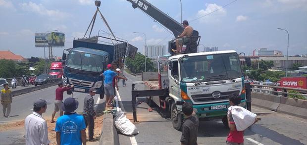 Xe tải rớt bánh lật trên quốc lộ 1A ở Sài Gòn, nhiều người thoát chết, giao thông ùn ứ kéo dài   - Ảnh 4.