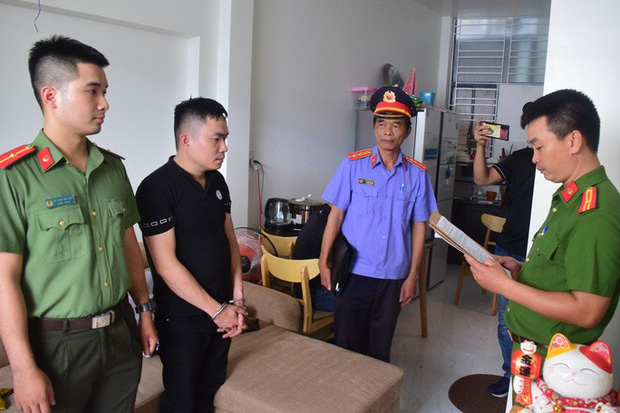 Đối tượng Lê Anh Tuấn (áo đen) bị công an bắt giữ