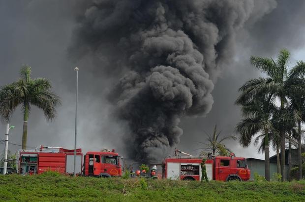 Đang cháy dữ dội tại kho hóa chất ở Long Biên, cột khói đen bốc cao hàng chục mét - Ảnh 4.