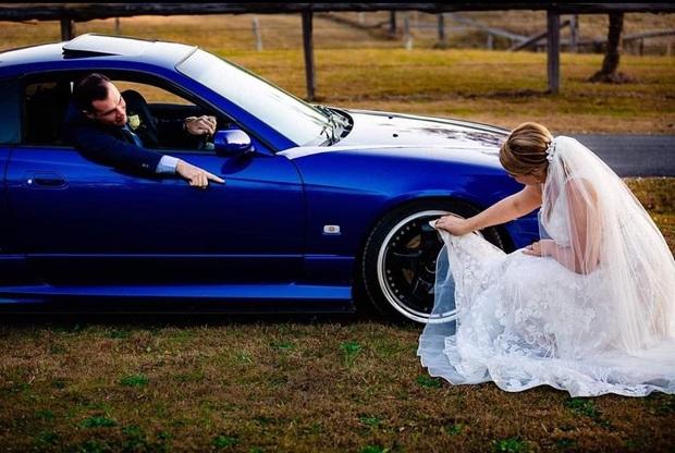 Bức ảnh cô dâu ngồi xuống đất, dùng vạt váy cưới trắng muốt lau bánh xe của chồng khiến dân mạng được phen tranh cãi kịch liệt - Ảnh 1.