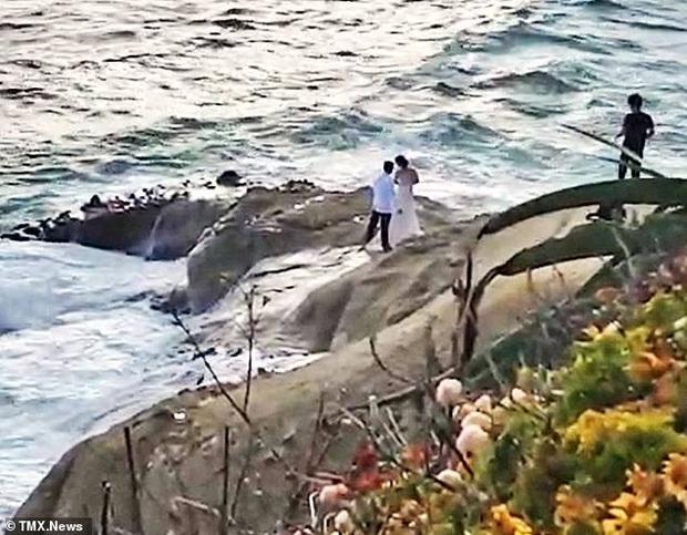 Ra bãi biển chụp ảnh cưới, cô dâu chú rể bị sóng cuốn phăng ra biển, khoảnh khắc con sóng lớn ập đến khiến mọi người thót tim - Ảnh 2.