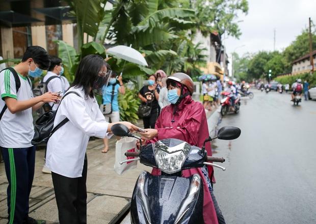 Vượt qua cơn mưa chiều, SGO48 đội ô đi phát khẩu trang cho sĩ tử - Ảnh 3.
