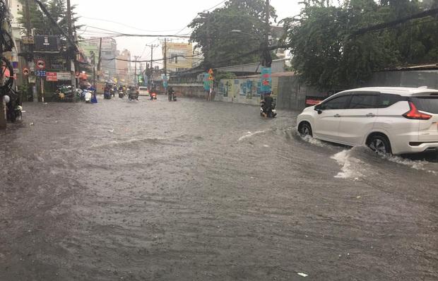 Nhiều tuyến đường ở Sài Gòn lại thành sông sau mưa lớn, các cửa hàng phải đóng cửa vì nước tràn vào nhà - Ảnh 1.