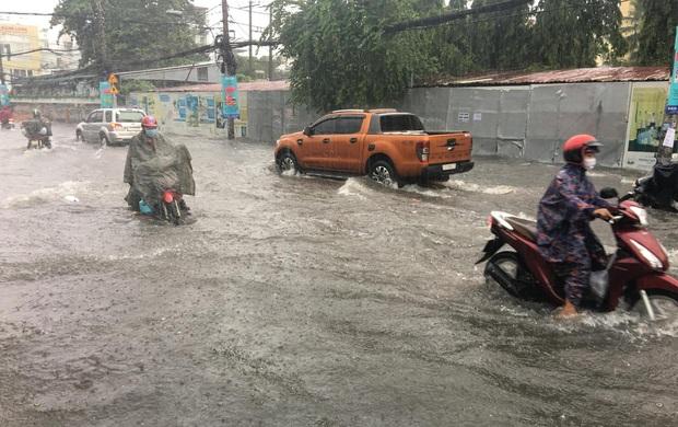Nhiều tuyến đường ở Sài Gòn lại thành sông sau mưa lớn, các cửa hàng phải đóng cửa vì nước tràn vào nhà - Ảnh 2.