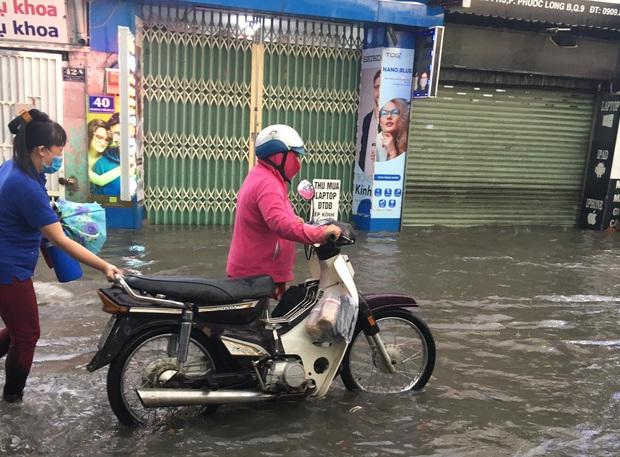 Nhiều tuyến đường ở Sài Gòn lại thành sông sau mưa lớn, các cửa hàng phải đóng cửa vì nước tràn vào nhà - Ảnh 4.