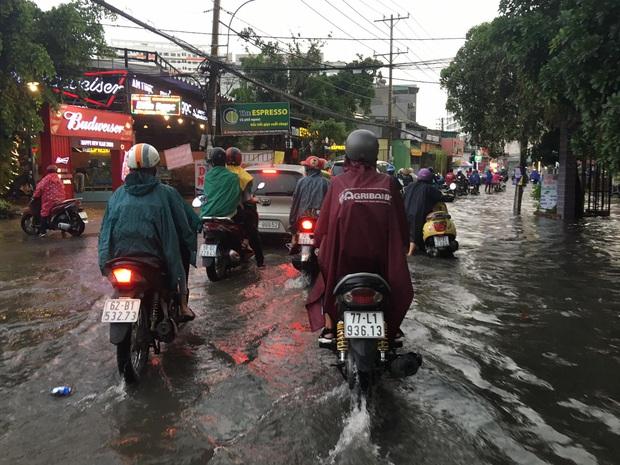 Nhiều tuyến đường ở Sài Gòn lại thành sông sau mưa lớn, các cửa hàng phải đóng cửa vì nước tràn vào nhà - Ảnh 8.