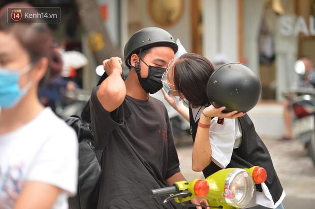 Cặp đôi hôn nhau cực ngọt qua lớp khẩu trang trước cổng trường thi THPT Quốc gia - Ảnh 1.