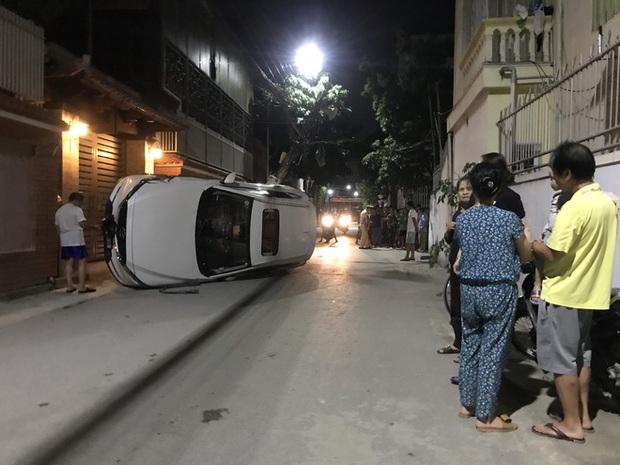 Xế hộp đâm gãy cột điện rồi lật nghiêng giữa đường, người trong xe bò ra từ cửa sổ trời - Ảnh 3.