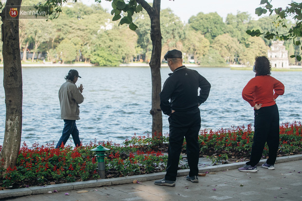 Ảnh: Hà Nội sáng đầu tuần rét lạnh dù có nắng, người dân trang bị áo ấm ra đường - Ảnh 6.