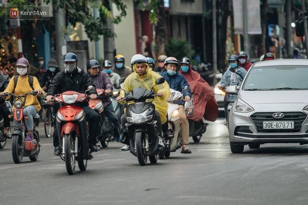 Chùm ảnh: Không khí lạnh rất mạnh tràn về, người dân Hà Nội co ro trong áo phao và những cái ôm - Ảnh 5.