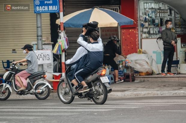 Chùm ảnh: Không khí lạnh rất mạnh tràn về, người dân Hà Nội co ro trong áo phao và những cái ôm - Ảnh 7.