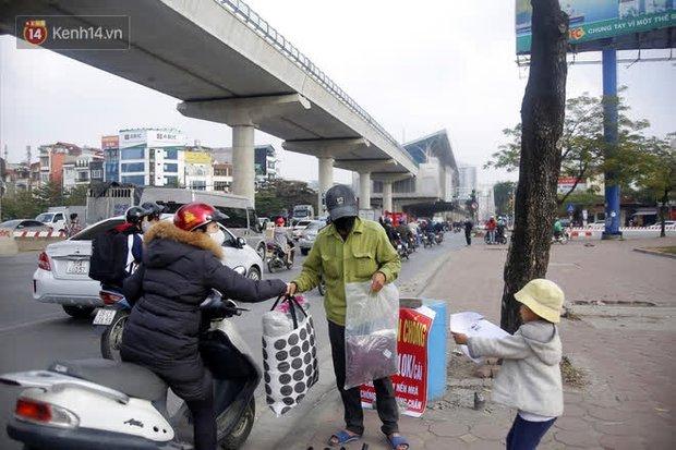 Gặp người cha gầy gò, ôm con nhỏ lang thang bán bọc chân chống xe máy gây xôn xao giữa phố Hà Nội - Ảnh 1.