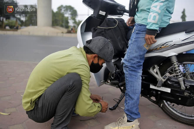 Gặp người cha gầy gò, ôm con nhỏ lang thang bán bọc chân chống xe máy gây xôn xao giữa phố Hà Nội - Ảnh 2.