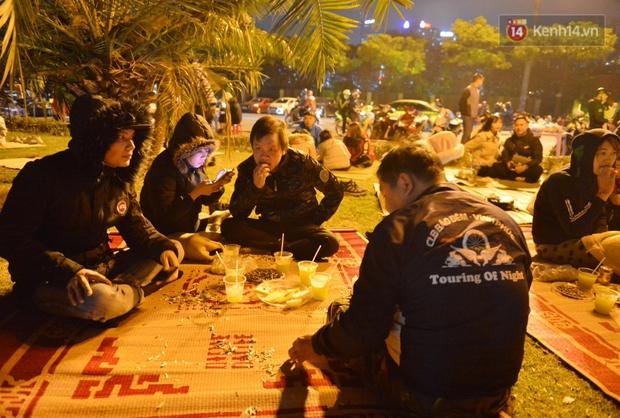 Người dân Hà Nội trải chiếu, ngồi la liệt trên bãi cỏ uống nước, cắn hướng dương canh pháo hoa đón năm mới 2021 - Ảnh 5.