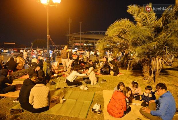 Người dân Hà Nội trải chiếu, ngồi la liệt trên bãi cỏ uống nước, cắn hướng dương canh pháo hoa đón năm mới 2021 - Ảnh 1.