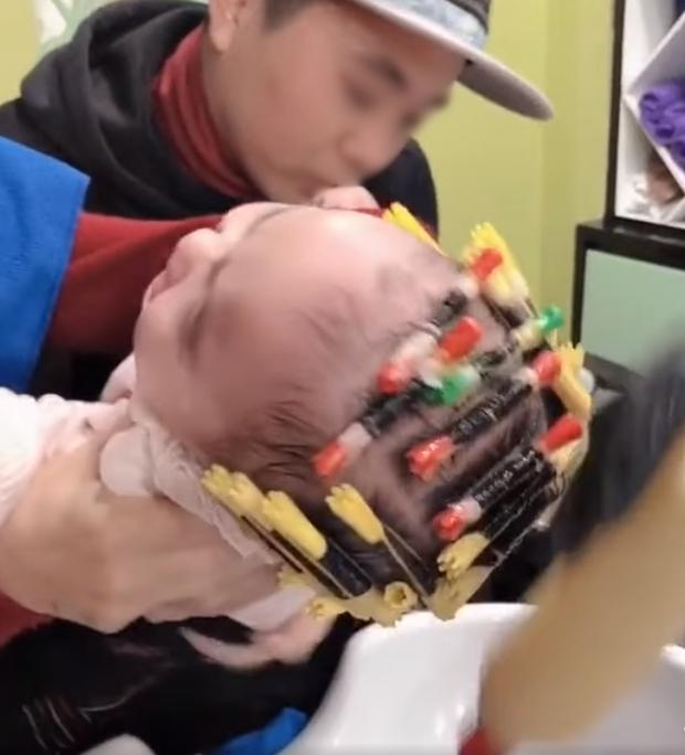 Cộng đồng mạng phẫn nộ xem clip bé gái 1 tuổi bị bế đi làm tóc xoăn, kẹp ống thít chặt tóc và đổ hóa chất đầy đầu - Ảnh 2.