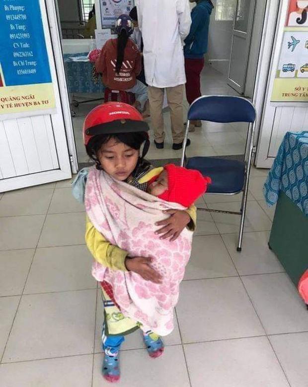 Xót xa hình ảnh bé gái 7 tuổi bế em đi tiêm phòng - Ảnh 1.