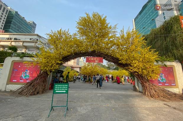 Bà đồ xinh đẹp mặc áo dài, viết thư pháp tại đường hoa mai ở Sài Gòn thu hút nhiều người - Ảnh 1.