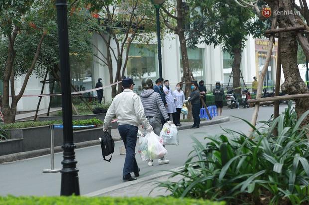 Cận cảnh phong toả toà T6 khu đô thị Times City sau ca Covid-19, người dân liên tục tiếp tế thực phẩm vào bên trong - Ảnh 9.