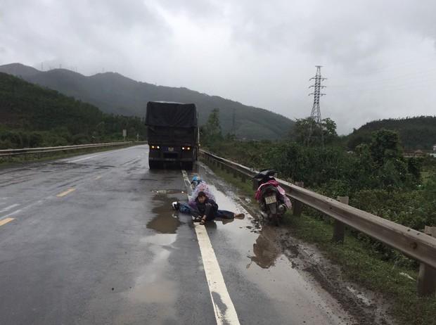 Tai nạn thương tâm: Hai mẹ con ngồi bệt xuống đường, ôm thi thể chồng khóc ngất giữa trời mưa lạnh - Ảnh 1.