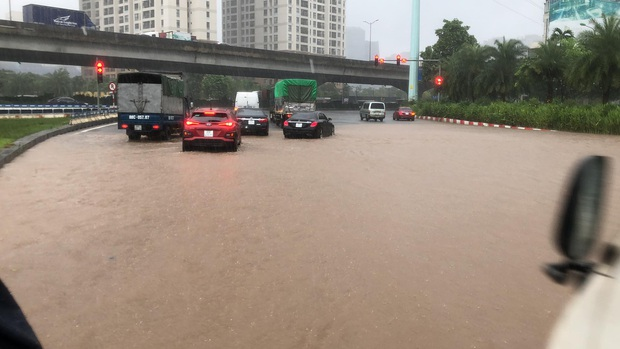 Ảnh: Mưa lớn kéo dài do ảnh hưởng của bão số 7, nhiều nơi ở Hà Nội ngập sâu, người dân chật vật di chuyển - Ảnh 1.
