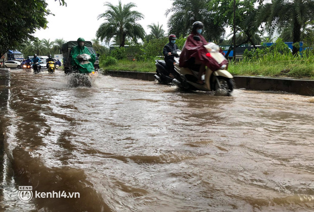 Ảnh: Mưa lớn kéo dài do ảnh hưởng của bão số 7, nhiều nơi ở Hà Nội ngập sâu, người dân chật vật di chuyển - Ảnh 2.