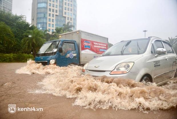 Ảnh: Mưa lớn kéo dài do ảnh hưởng của bão số 7, nhiều nơi ở Hà Nội ngập sâu, người dân chật vật di chuyển - Ảnh 4.