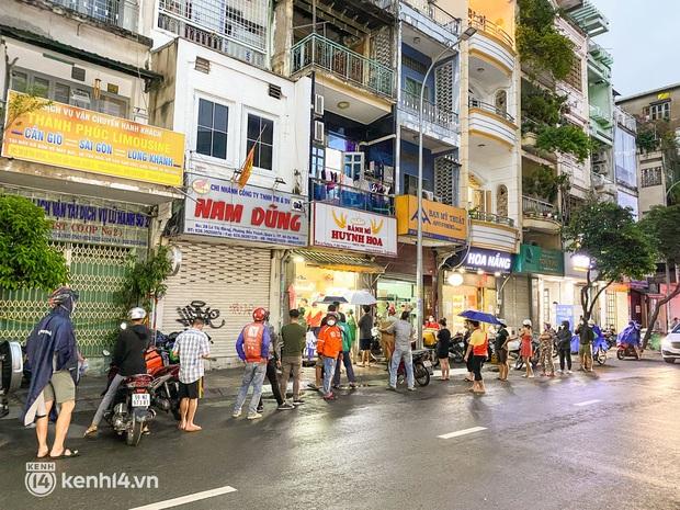 NGAY LÚC NÀY: Hàng chục người xếp hàng dưới mưa mua ổ bánh mì đắt nhất Sài Gòn, có khách hốt chục cái ăn trả thù mùa dịch! - Ảnh 3.