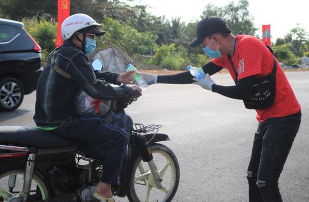 Dễ thương như người miền Tây: Cả nhà cùng nhau đứng bên đường, tặng bánh và nước miễn phí cho người lao động về quê ăn Tết - Ảnh 2.