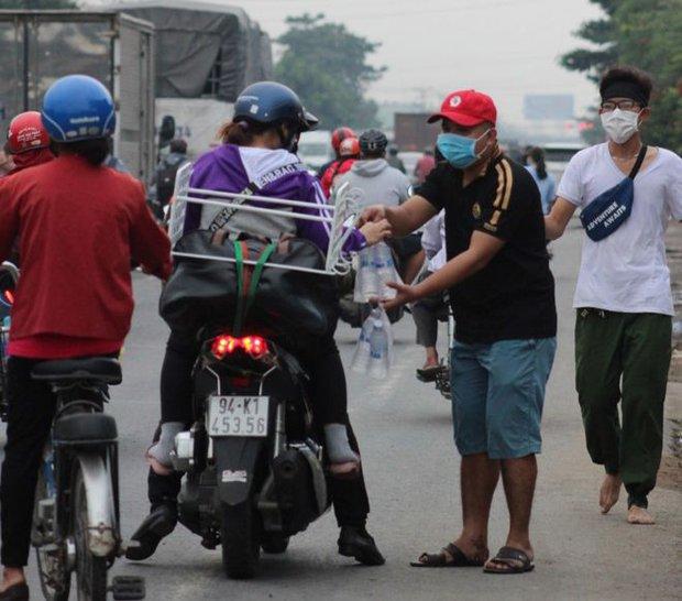 Dễ thương như người miền Tây: Cả nhà cùng nhau đứng bên đường, tặng bánh và nước miễn phí cho người lao động về quê ăn Tết - Ảnh 1.