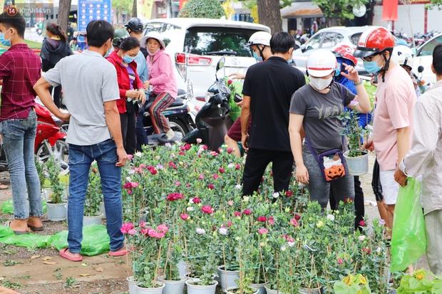 ẢNH: Sau khi tiểu thương ở Sài Gòn vứt bỏ hoa ế, nhiều người dân tranh thủ đến xin đất, lượm hoa mang về trưa 30 Tết - Ảnh 1.