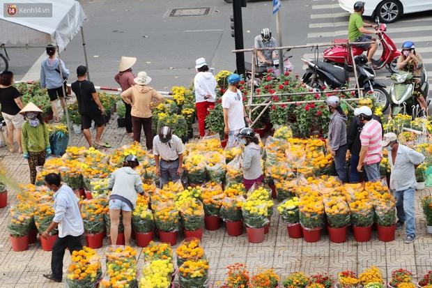 ẢNH: Sau khi tiểu thương ở Sài Gòn vứt bỏ hoa ế, nhiều người dân tranh thủ đến xin đất, lượm hoa mang về trưa 30 Tết - Ảnh 7.