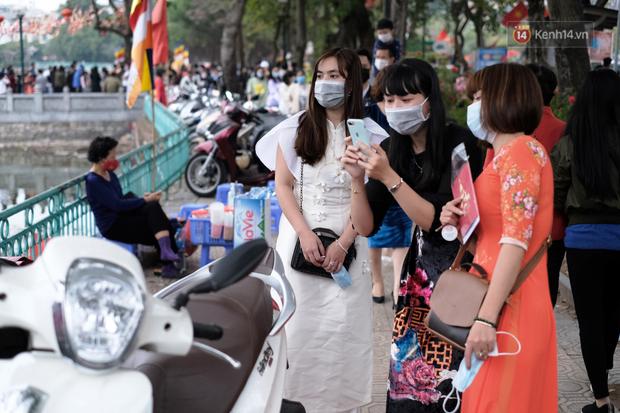 Chùm ảnh: Người dân đeo khẩu trang phòng dịch, xúng xính váy áo xuống phố dạo chơi chiều mùng 2 Tết - Ảnh 15.