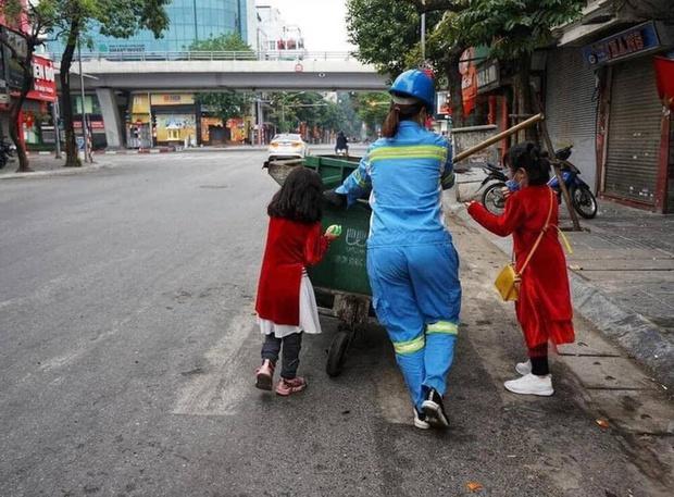 Người mẹ lao công trong bức ảnh cùng 2 con đi làm ngày mùng 1 Tết: Trẻ con thơ ngây lắm, chỉ cần được đi theo mẹ đã thích rồi - Ảnh 1.