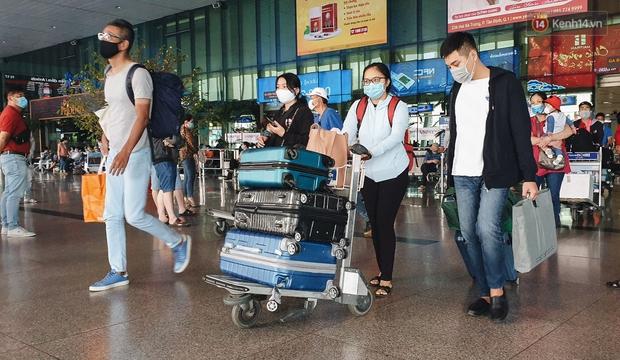 Chùm ảnh: Người dân mặc đồ bảo hộ kín mít trên những chuyến bay trở về Sài Gòn sau kỳ nghỉ Tết Nguyên đán - Ảnh 1.